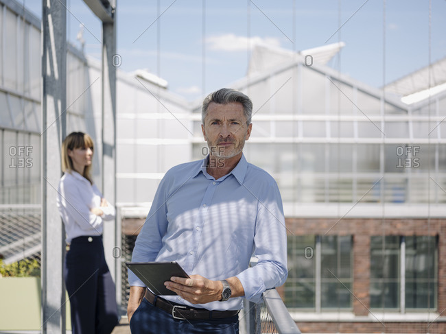 Confident businessman holding digital tablet while standing with female coworker in greenhouse
