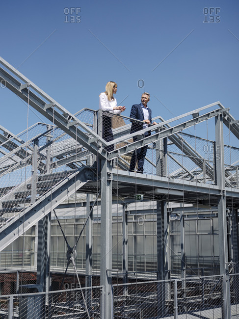 Colleagues discussing while standing on built structure against clear sky