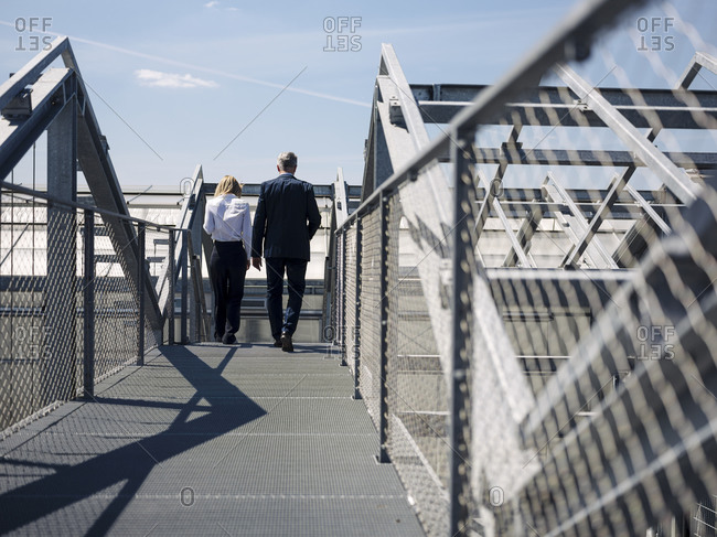 Colleagues discussing while walking on footbridge during sunny day