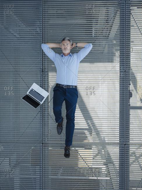 Businessman with hands behind head lying on metallic floor in greenhouse