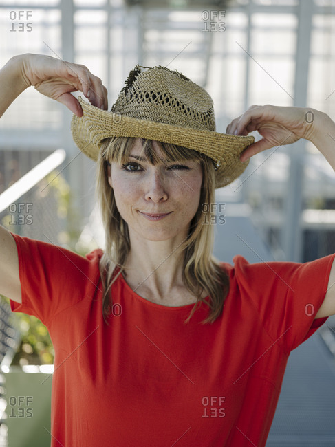 Close-up of businesswoman wearing hat while standing in plant nursery