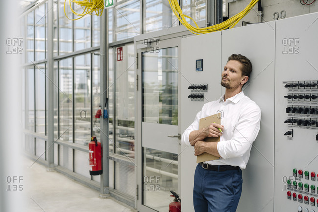 Thoughtful businessman holding clipboard while leaning on control panel in greenhouse