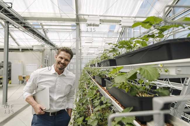 Smiling male owner with laptop standing by plants in greenhouse