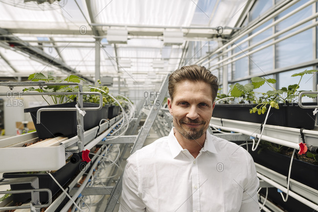 Smiling male entrepreneur standing amidst plants growing in greenhouse