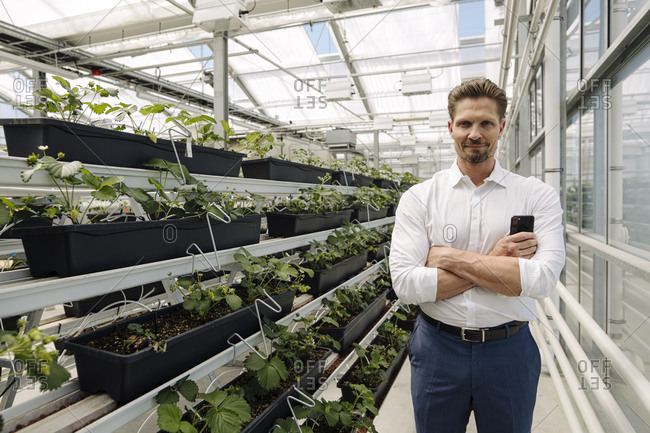 Confident male entrepreneur with arms crossed standing by plants in greenhouse