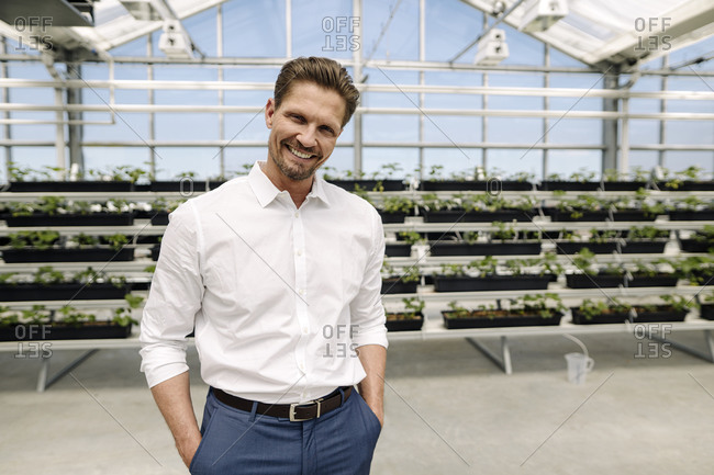 Smiling male entrepreneur with hands in pockets standing against plants at greenhouse