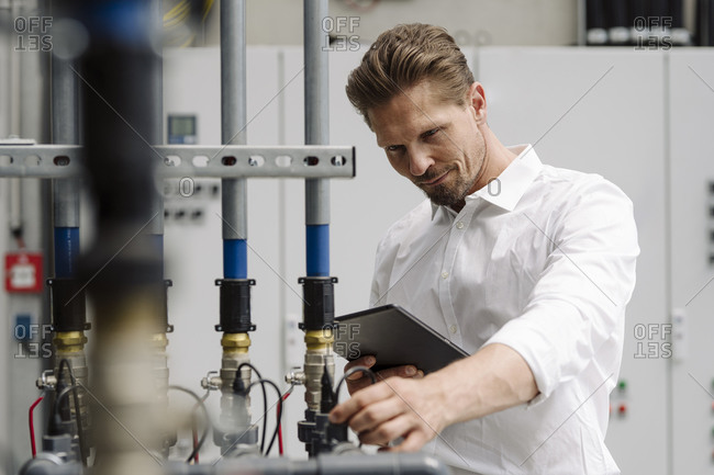 Businessman holding digital tablet while examining agricultural machinery in plant nursery