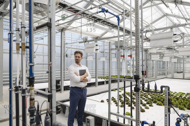 Male entrepreneur with digital tablet standing in plant nursery