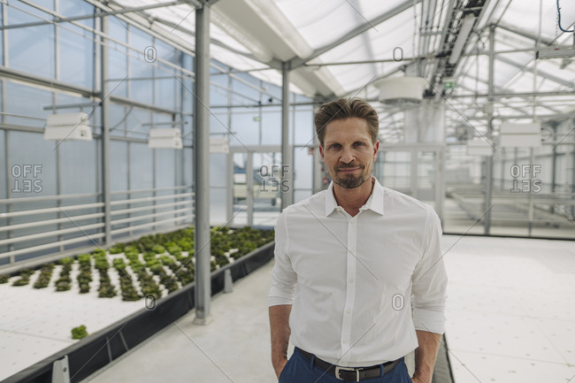 Confident male owner with hands in pockets standing at greenhouse