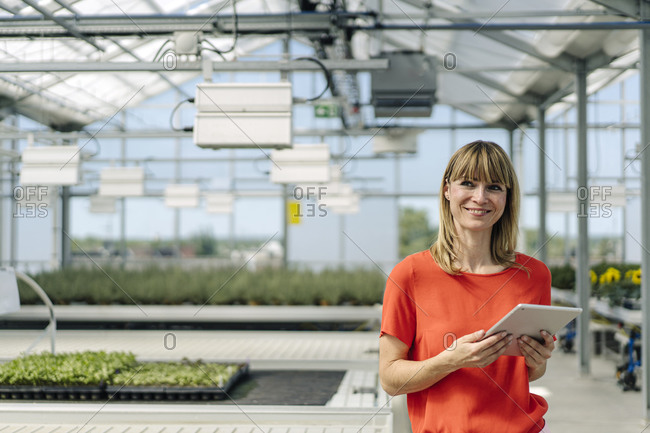 Smiling female entrepreneur using digital tablet while standing in plant nursery