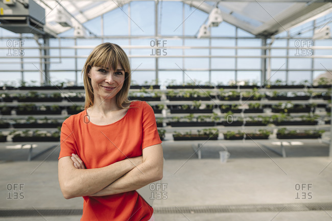 Smiling female entrepreneur with arms crossed standing against plants at nursery
