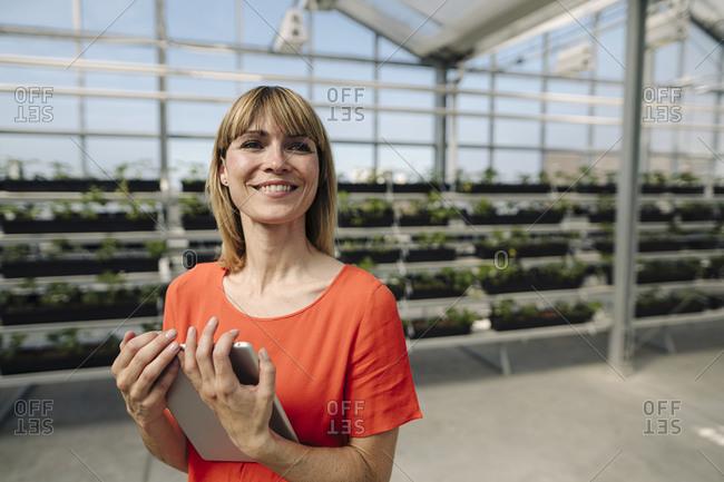 Smiling female entrepreneur holding digital tablet looking away in plant nursery