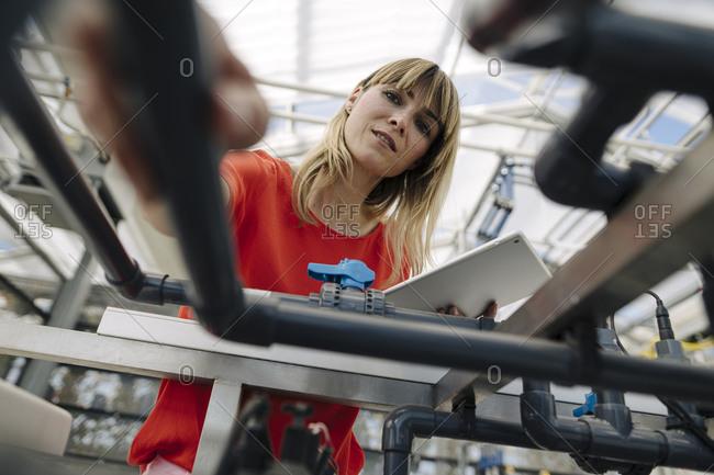 Female entrepreneur with digital tablet examining equipment in plant nursery