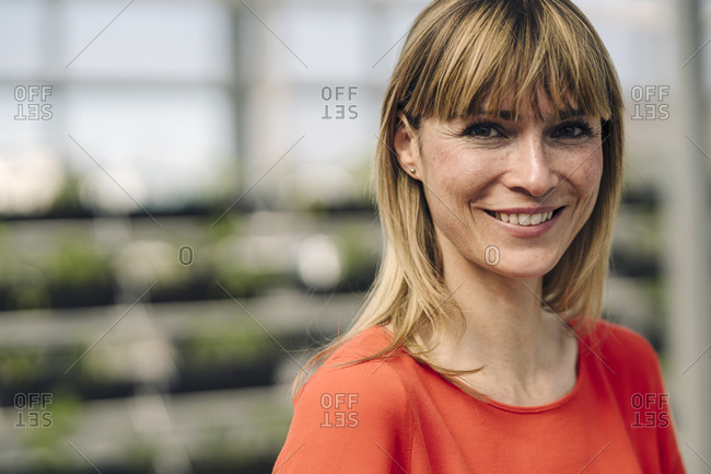Close-up of smiling female entrepreneur with blond hair in plant nursery