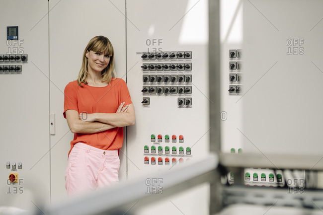 Female entrepreneur with arms crossed standing by control panel in greenhouse