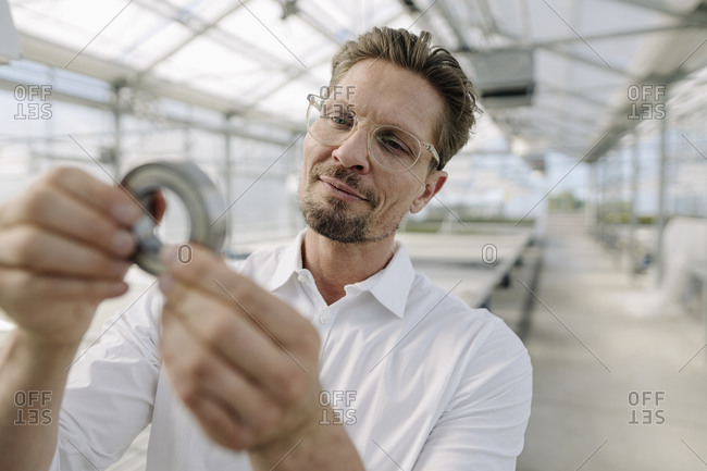 Close-up of businessman wearing eyeglasses examining equipment in plant nursery