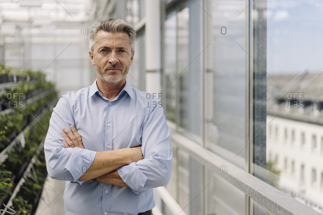 Male professional with arms crossed standing in plant nursery