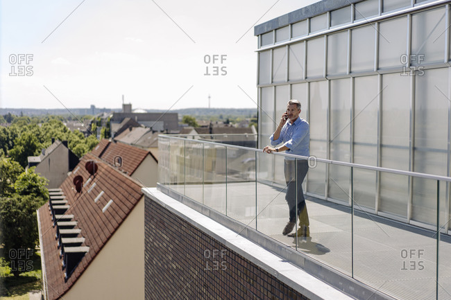 Businessman talking over smart phone while standing in balcony against sky on sunny day