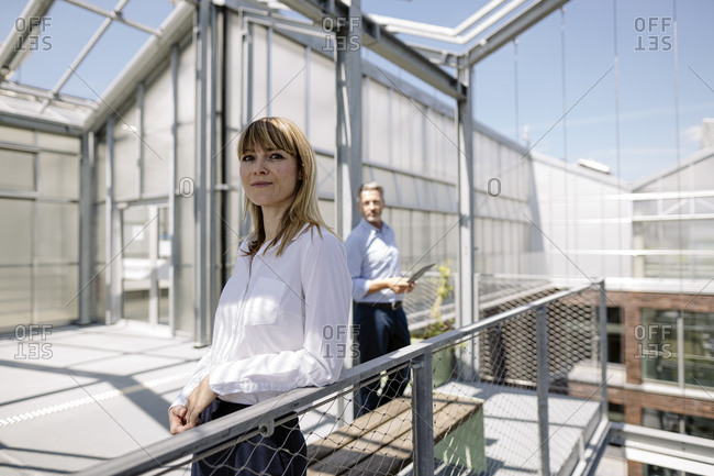 Confident businesswoman standing by railing with male coworker in background at greenhouse