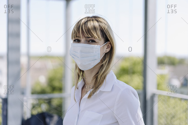 Close-up of female entrepreneur wearing mask standing in greenhouse