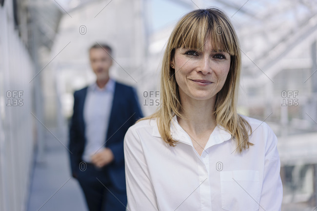 Close-up of smiling businesswoman with male coworker in background at greenhouse