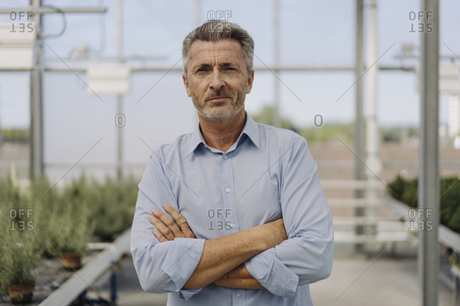 Confident male professional with arms crossed standing in plant nursery