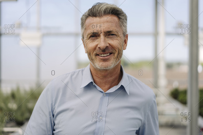 Close-up of smiling male professional standing in plant nursery