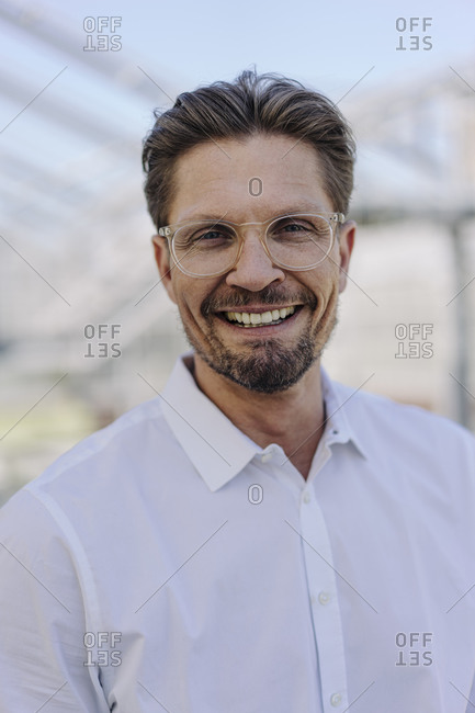 Close-up of smiling male professional wearing eyeglasses in plant nursery