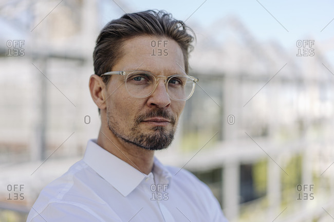 Close-up of serious male professional wearing eyeglasses in plant nursery