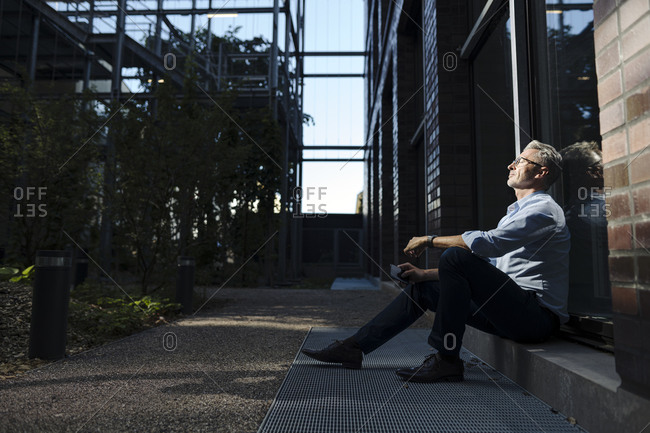 Businessman with eyes closed sitting outside office building