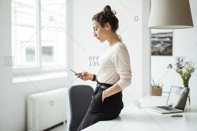 Businesswoman with hand in pocket using smart phone while standing by table