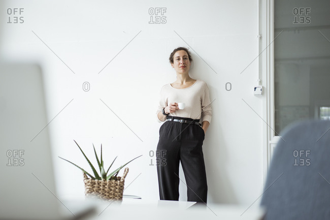 Confident businesswoman with hand in pocket holding coffee cup while standing against white wall