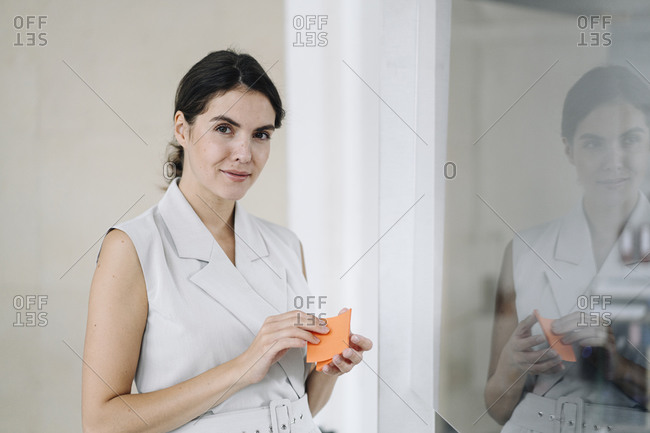 Woman holding sticky notes while standing by glass wall at office