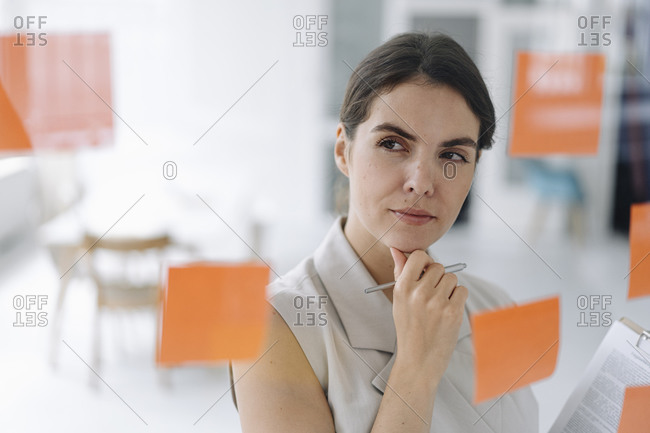 Thoughtful businesswoman standing with hand on chin at office
