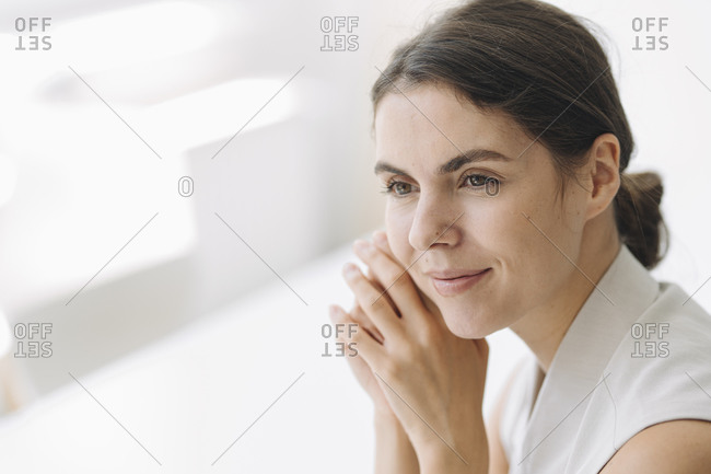 Beautiful woman with hand on chin sitting at office