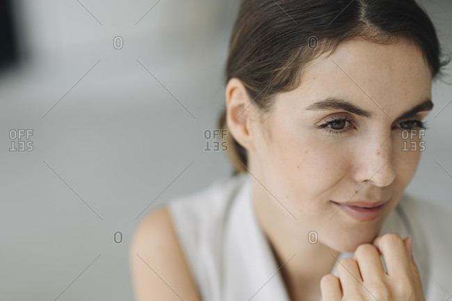 Thoughtful young woman with hand on chin sitting at office