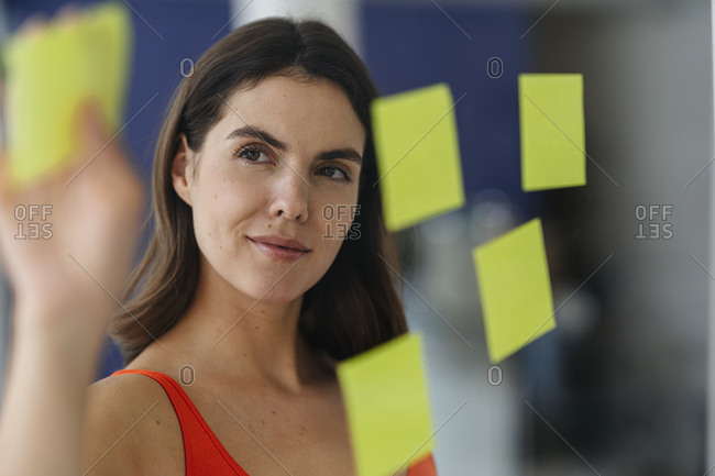 Woman putting sticky note on glass wall at home