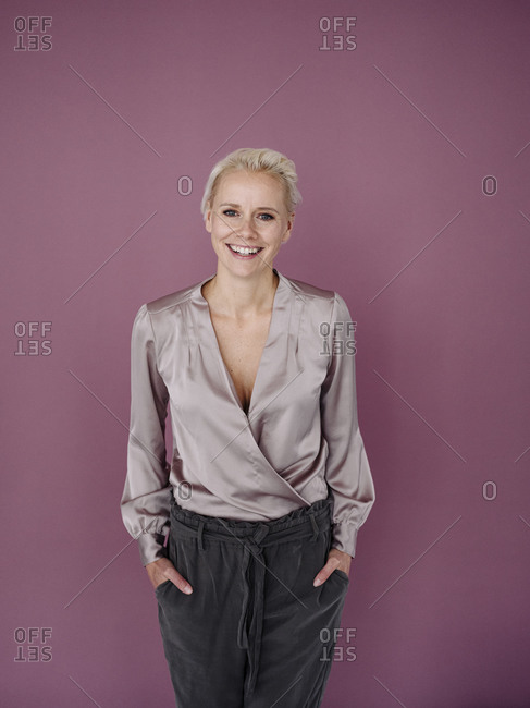 Smiling businesswoman with hands in pockets standing against purple background