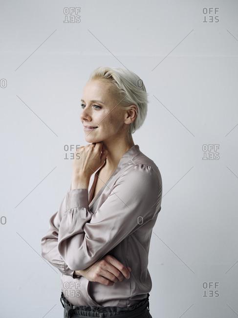 Thoughtful businesswoman with hand on chin standing against white wall in office