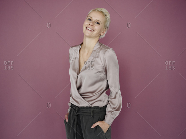 Smiling female entrepreneur with hands in pockets standing against purple background