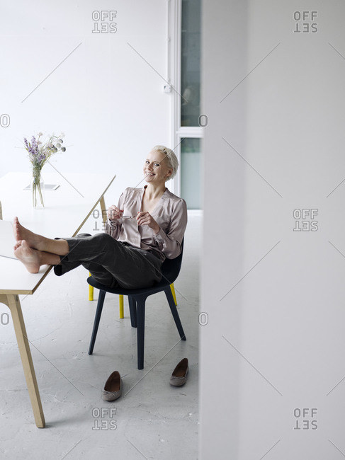 Smiling businesswoman with feet up relaxing on chair in loft office
