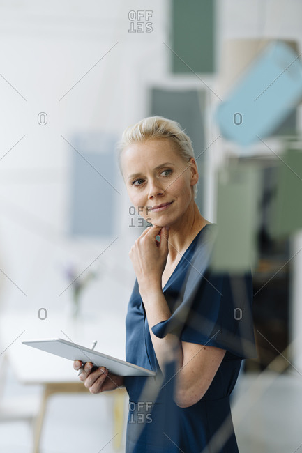 Thoughtful businesswoman with digital tablet looking away while standing in loft