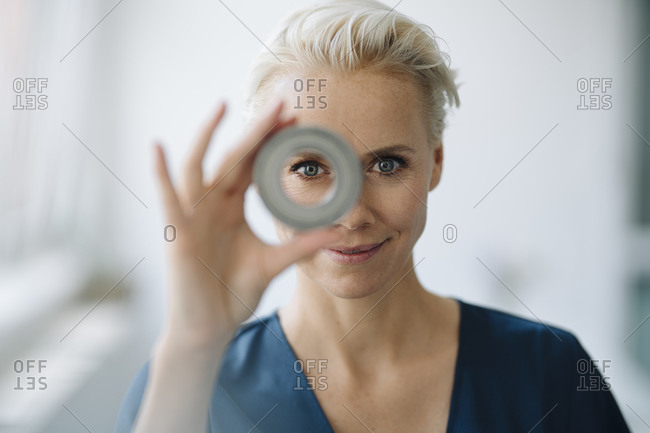Close-up of smiling businesswoman looking through object in office