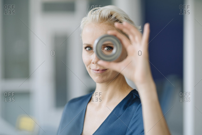 Close-up of confident businesswoman looking through object in office