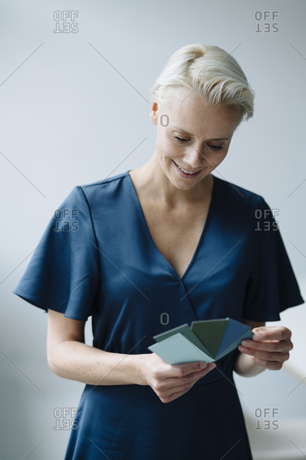 Businesswoman choosing color swatch while standing against wall in office