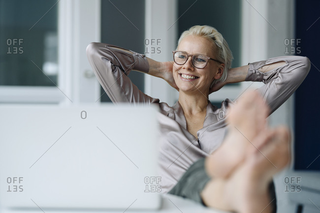 Thoughtful businesswoman with hands behind head relaxing at desk in office