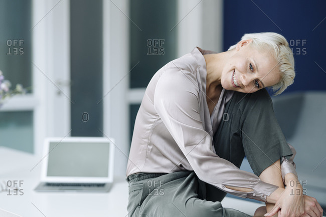 Smiling businesswoman contemplating while sitting on desk in office