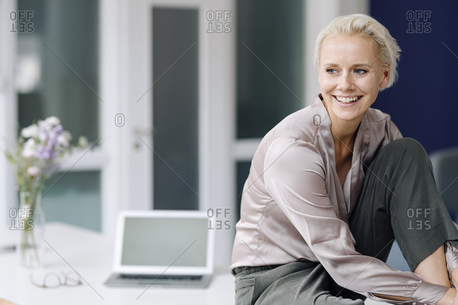 Smiling businesswoman contemplating while sitting on desk in loft office