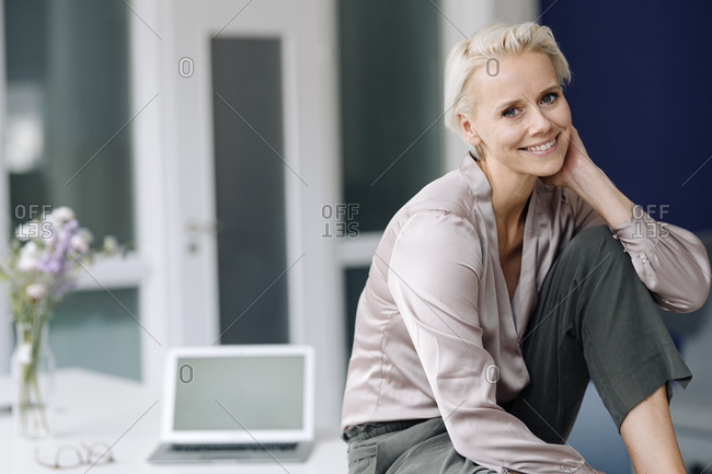 Smiling businesswoman with laptop relaxing on desk in loft office