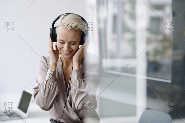 Smiling female entrepreneur with eyes closed listening music over headphones while sitting in loft